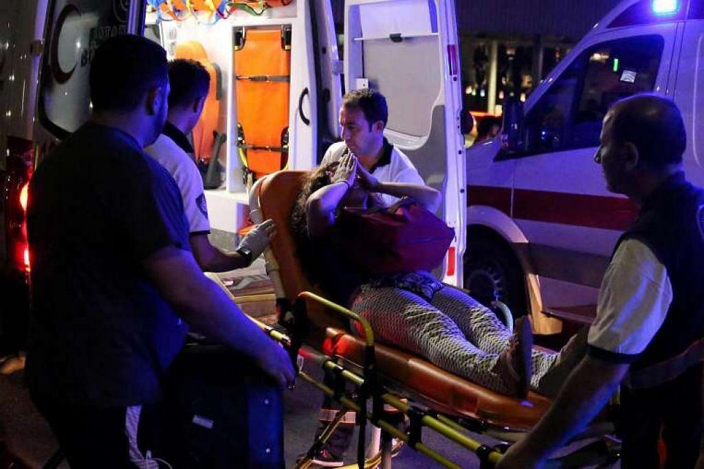 Seorang wanita yang cedera di muka dibawa oleh paramedik ke dalam ambulans di lapangan terbang Istanbul Ataturk, Turkey.
