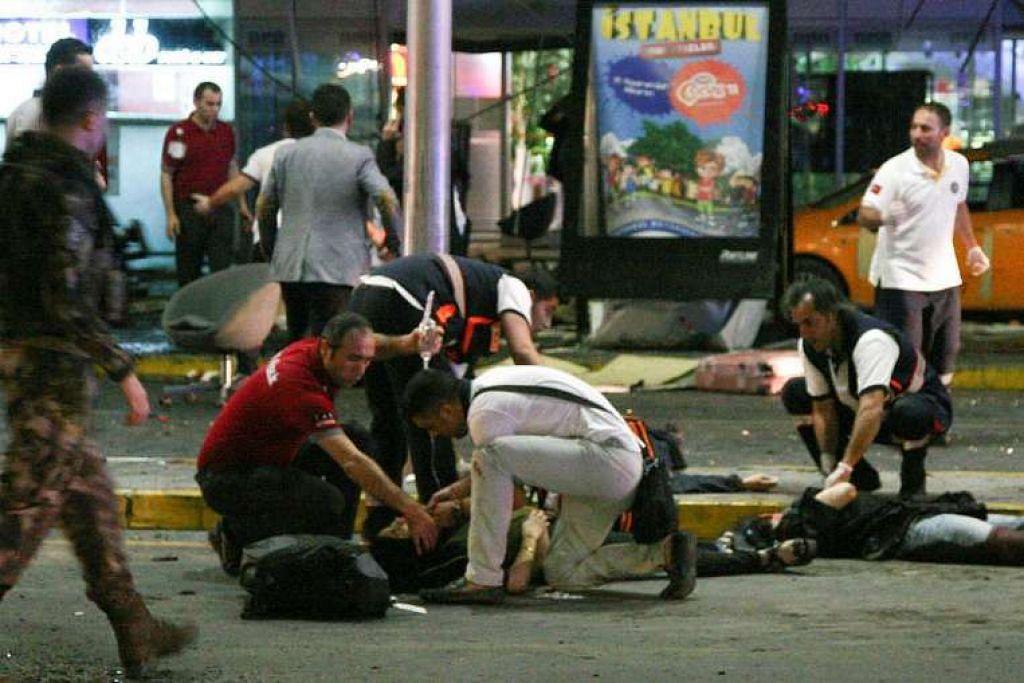 Paramedics merawat mangsa cedera di luar lapangan terbang Istanbul Ataturk, Turkey pada 28 Jun 28.