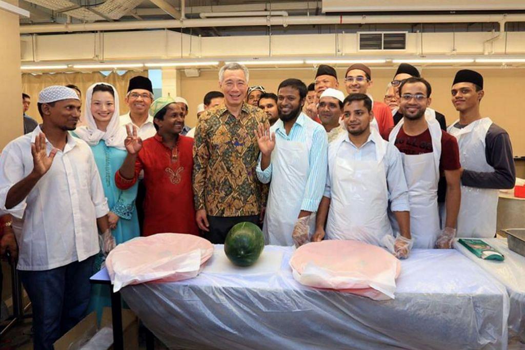 BERSAMA SUKARELAWAN: Encik Lee bersama warga Bangladesh yang membantu menjayakan majlis iftar di Masjid Al-Islah. Ramai warga Bangladesh menyumbang tenaga sebagai sukarelawan di masjid itu. - Foto FACEBOOK PM LEE