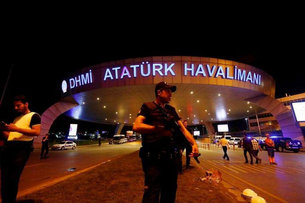 Seorang pegawai polis rusuhan berdiri berkawal di pintu masuk Lapangan Terbang Ataturk di Istanbul,