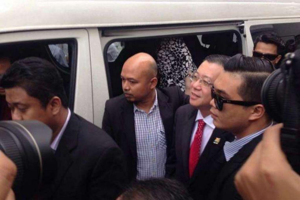 Encik Lim Guan Eng (bertali leher merah)  tiba di mahkamah.
