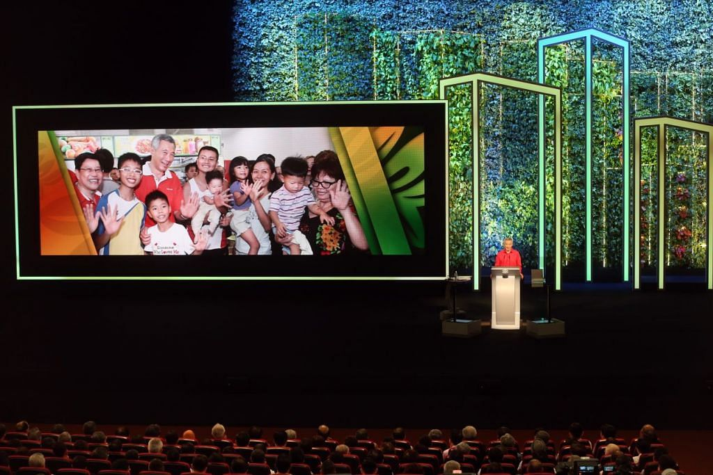 Perdana Menteri Lee Hsien Loong menyampaikan ucapan SG50 Rapat Hari Kebangsaan di ITE College Central pada 23 Ogos 2015. Gambar Encik Lee bersama keluarga yang beliau sebut dalam ucapan beliau dipapar pada skrin.