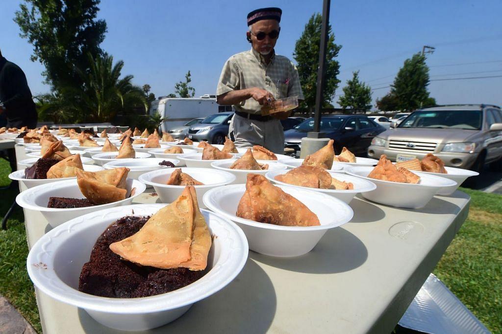 DI CALIFORNIA: Encik Arshad Farooq membantu menyediakan juadah untuk Aidilfitri termasuk samosa dan kek coklat di Masjid Baitul Hameed in Chino, California. - Foto AFP