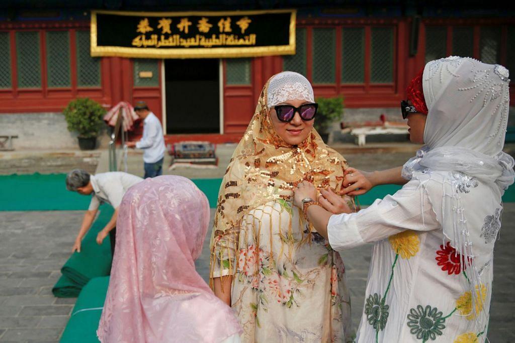 DI BEIJING: Kaum wanita memperkemaskan diri sementara kaum lelaki membentang tikar bersiap untuk solat Raya di masjid bersejarah Niujie di Beijing. - Foto REUTERS