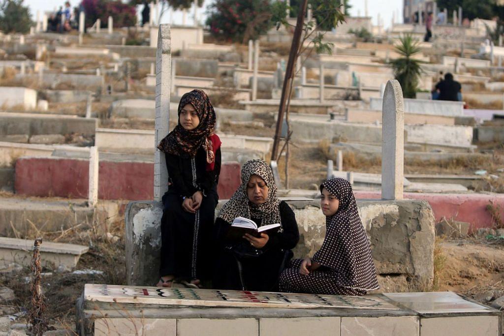 DI PALESTIN: Seorang wanita Palestin membaca Al-Quran di pusara anaknya di Bandar Gaza, kelmarin.  - Foto REUTERS