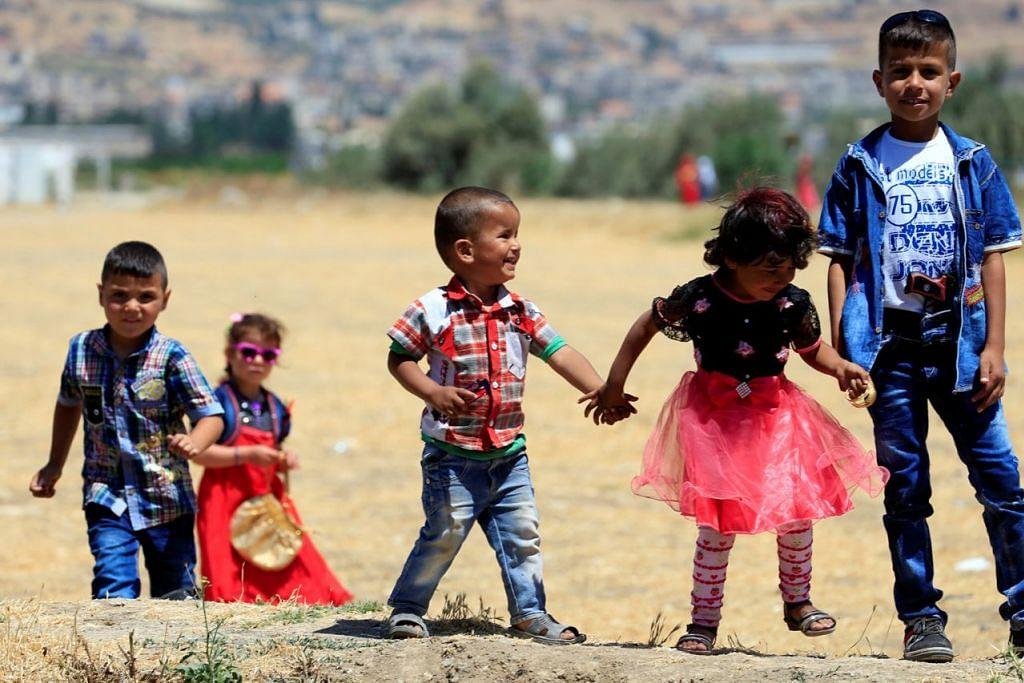DI LEBANON: Kanak-kanak Syria yang berlindung di khemah pelarian di kampung Delhemiyeh dekat Lebanon menyambut Raya dengan pakaian berwarna-warni. - Foto REUTERS