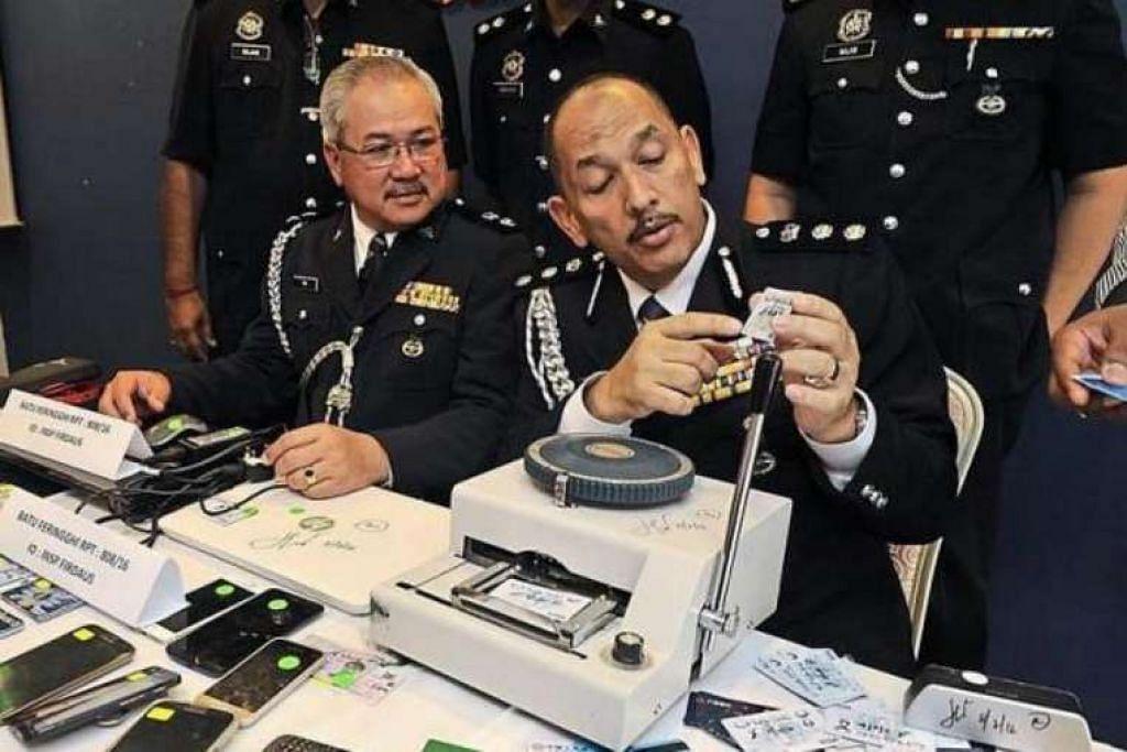 Timbalan Ketua Jabatan Siasatan Jenayah Komersial Pulau Pinang, Superintenden Teh Eng Hin (kiri), dan ACP Mior melihat kad kredit klon semasa sidang media di Ibu Pejabat Polis George Town.