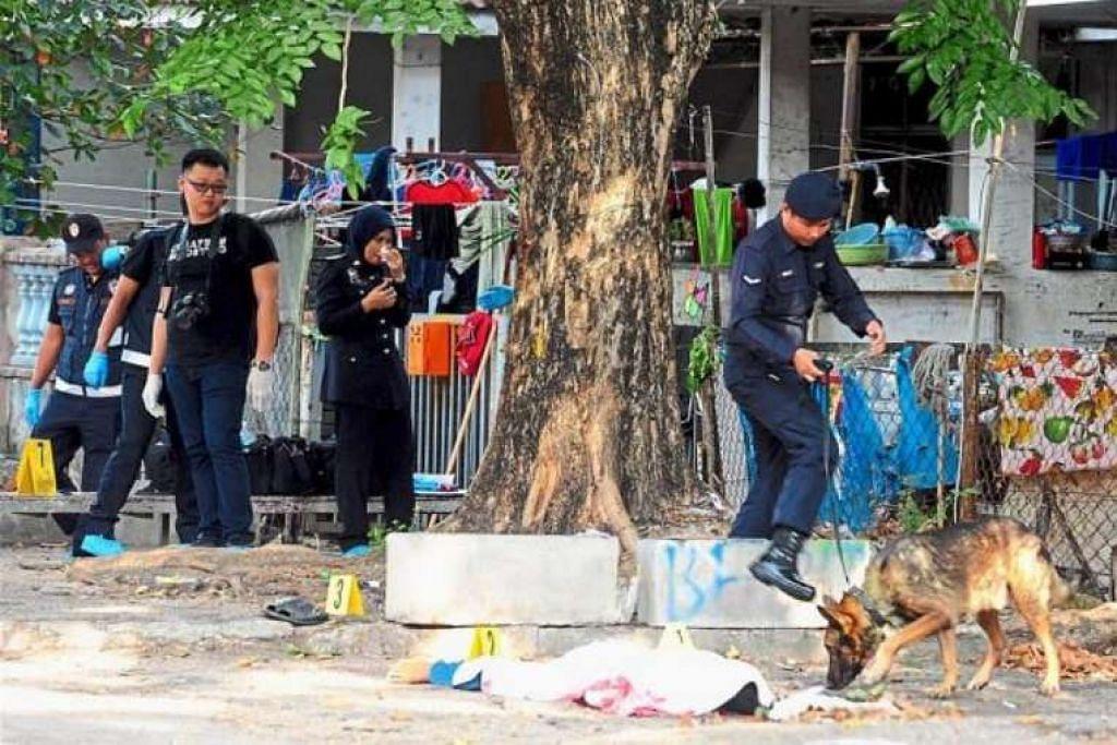 Pegawai polis dan unit anjing  K-9  memeriksa di luar rumah tempat seorang pekerja Myanmar ditemui mati.