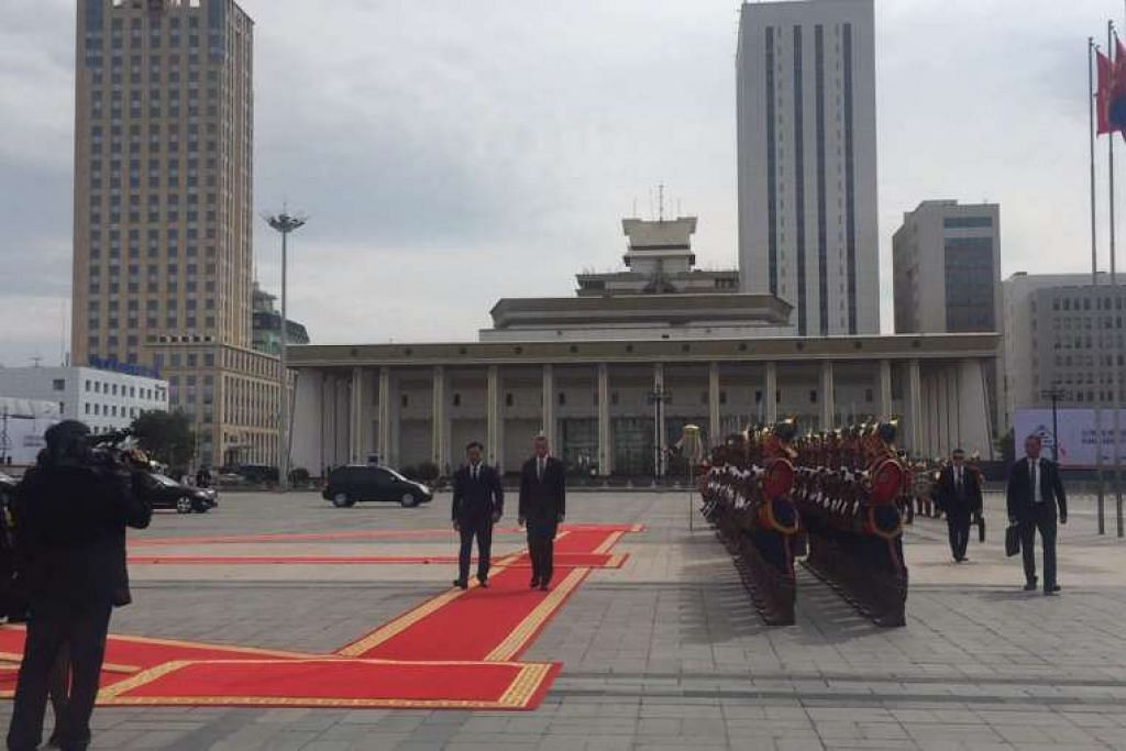 Perdana Menteri Lee Hsien Loong (kanan) memeriksa barisan kawalan kehormat dengan diiringi  rakan sejawatannya dari Mongolia, Encik Jargaltulga Erdenebat.