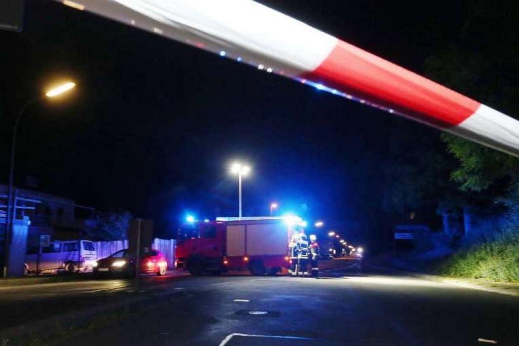 Anggota bomba berdiri di sekatan jalan raya di Wuerzburg, Jerman, selepas seorang remaja menyerang penumpang kereta api dengan kapak.