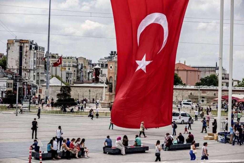 Penduduk tempatan dan pelawat duduk di bawah bendera kebangsaan gergasi Turkey di Dataran Taksim di Istanbul.