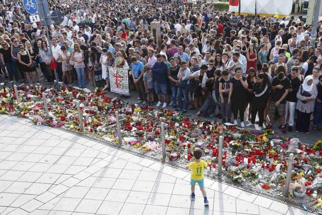 Orang ramai memperingati mangsa serangan Munich di luar pusat beli-belah Olympia Ahad (24 Julai).