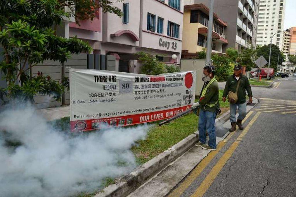 Pekerja kontraktor NEA menjalankan pengasapan terhadap nyamuk Aedes di Lorong 30 Geylang.