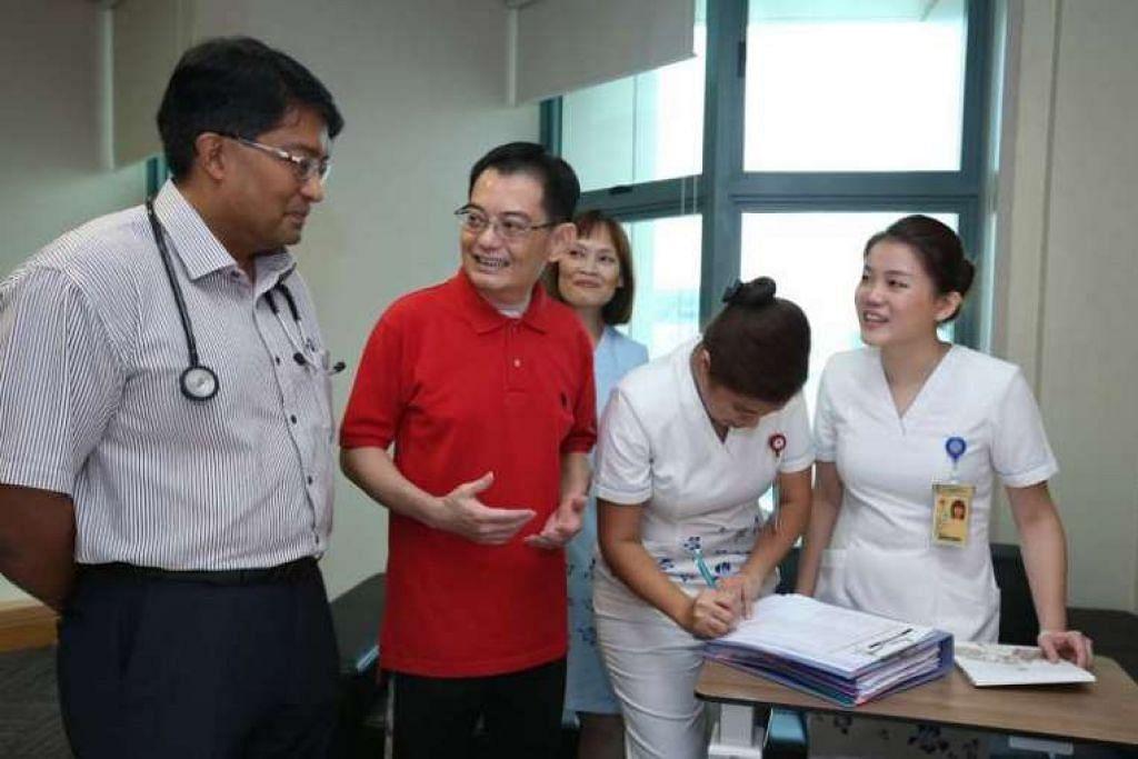 Menteri Kewangan Heng Sweet Keat bercakap kepada seorang doktor pada hari beliau dibenarkan keluar  Hospital Tan Tock Seng.