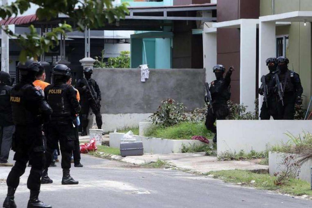 Skuad polis antipengganasan Indonesia mencari bukti dalam satu serbuan di kawasan perumahan di Batam Center di Batam pada 5 Ogos.
