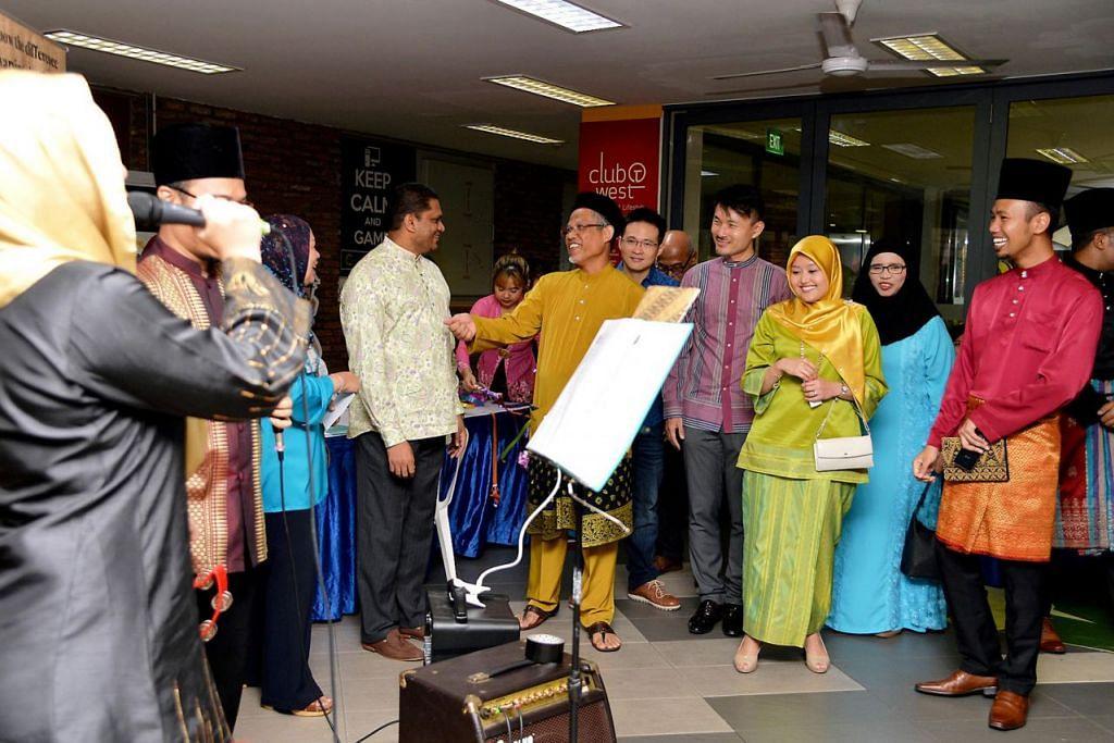 FOKUS PADA MUZIK: Encik Masagos (berbaju kurung kuning) berseloroh dengan seorang penduduk Tampines semasa pelancaran Bulan Bahasa di estet perumahan itu yang tahun ini memberi fokus kepada kegemilangan muzik Melayu. Turut hadir dalam majlis itu ialah Cik Rahayu (berbaju hijau muda) dan Encik Baey (berbaju ungu). – Foto M.O. SALLEH