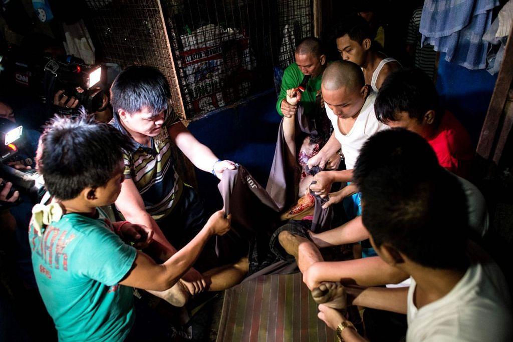 Penduduk mengangkat mayat seorang suspek pengedar dadah yang dibunuh oleh lelaki bersenjata tidak dikenali di Manila pada 14 September 2016.