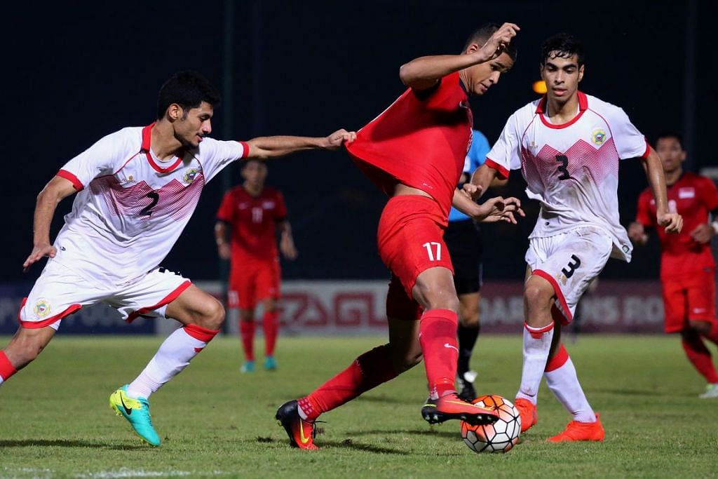 Seorang pemain pasukan bawah 19 tahun Bahrain menarik baju Irfan Fandi untuk menghalang pemain skuad bawah 19 tahun Singapura itu membuat jaringan semasa satu perlawanan persahabatan antarabangsa di Stadium Choa Chu Kang pada 4 September 2016.