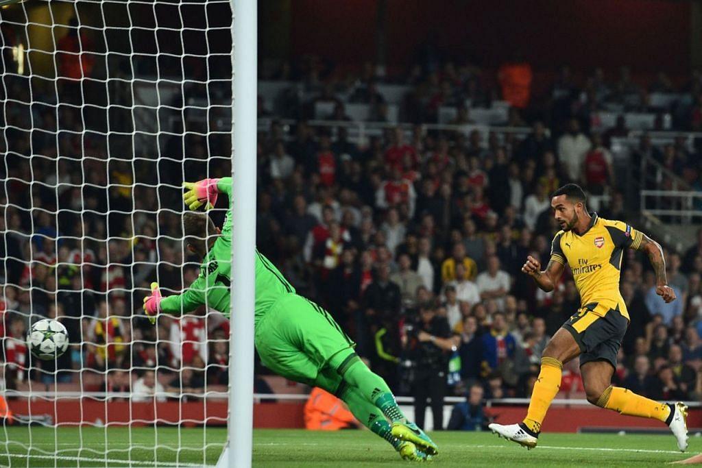 TANGKAS BERTINDAK: Bintang Arsenal, Theo Walcott (jersi kuning), menanduk gol pembukaan pasukannya semasa menentang FC Basel. – Foto AFP