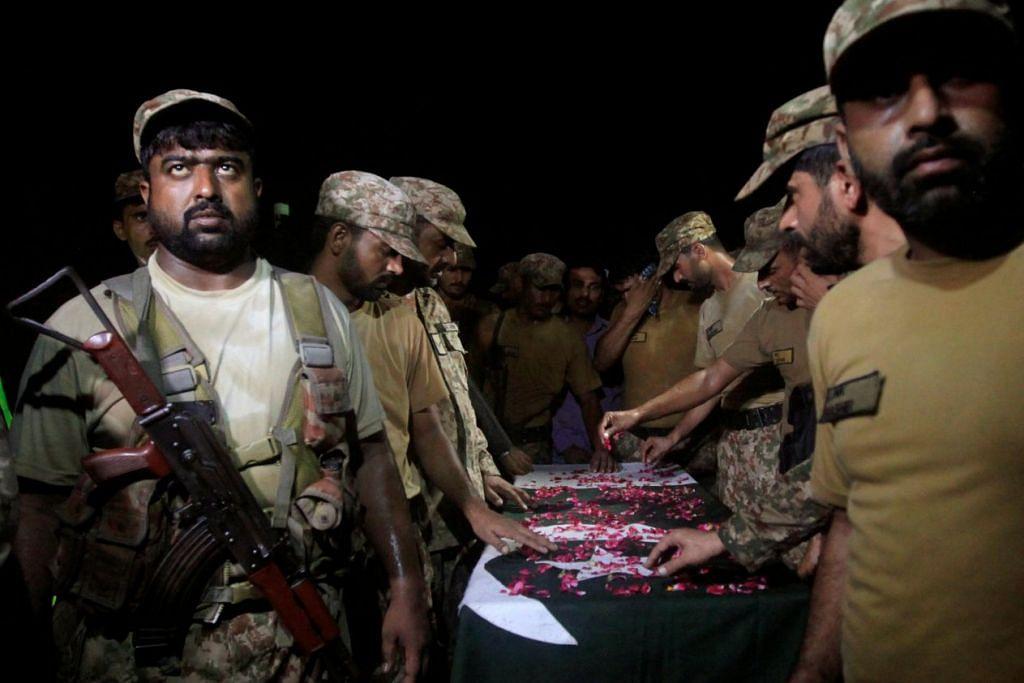 Askar Pakistan menjaga jenazah seorang rakan mereka, Imtiaz, yang terbunuh dalam serbuan rentas  sempadan oleh India di bahagian Khasmir yang dikuasai Pakistan pada Khamis (29 Sep), semasa pengebumian beliau di Faisalabad, Pakistan.