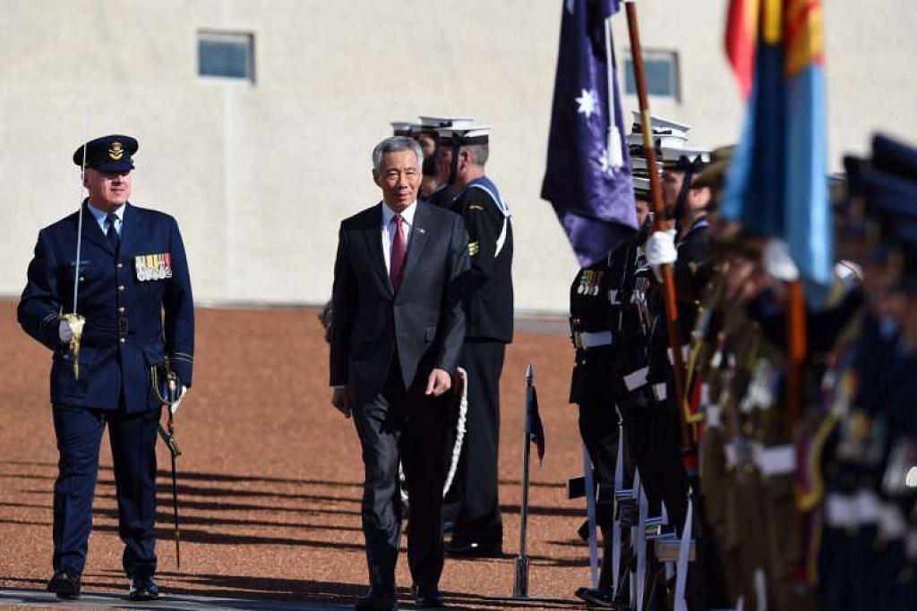 Encik Lee Hsien Loong memeriksa kawalan kehormatan semasa sambutan istiadat di Bangunan Parlimen di Canberra.