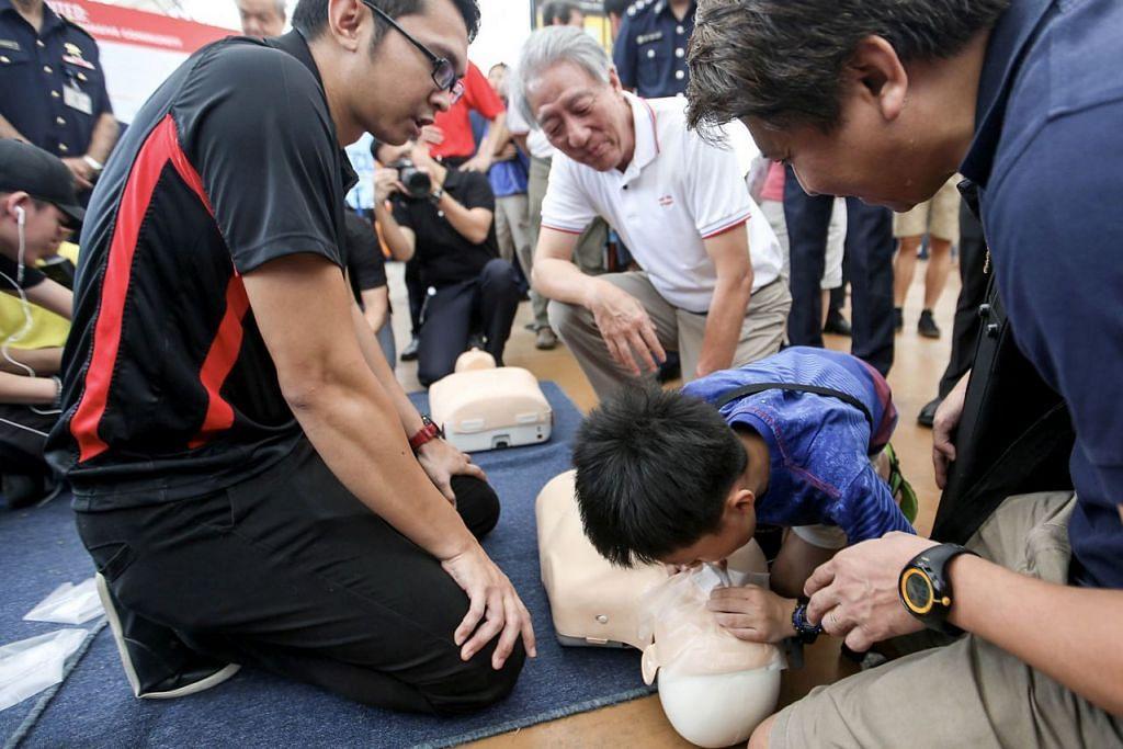 BERSEDIA HADAPI KECEMASAN: Encik Teo (berbaju putih) menyaksikan seorang kanak-kanak lelaki memberi bantuan pernafasan kecemasan di Hari Kesediaan Kecemasan Pasir Ris West semalam. – Foto ZAOBAO