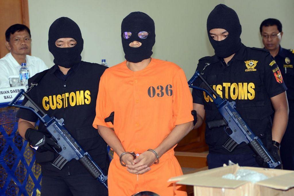 Seorang warga Singapura, Muhammad Faliq Nordin, diiringi pegawai kastam semasa sidang media berikutan penangkapannya di Denpasar, ibu negeri Bali, bagi kesalahan dadah pada 19 September 2016.