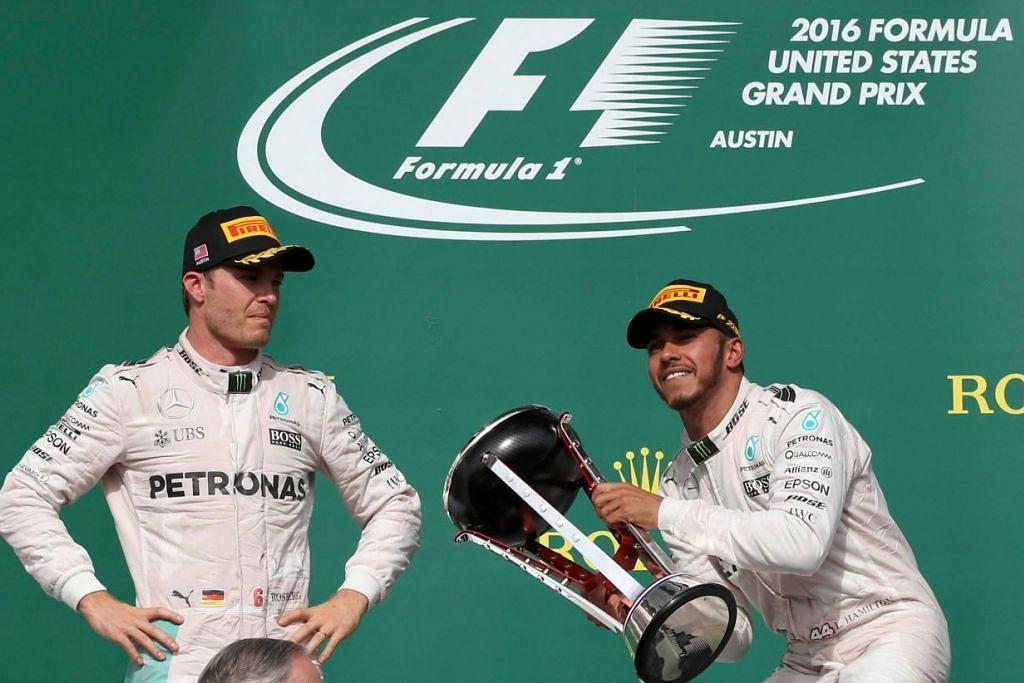 Lewis Hamilton dengan trofi Grand Prix Amerika di Litar Amerika di Austin pada 23 Okt, dengan diperhatikan pemenang tempat kedua, rakan sepasukan Mercedesnya, Nico Rosberg.