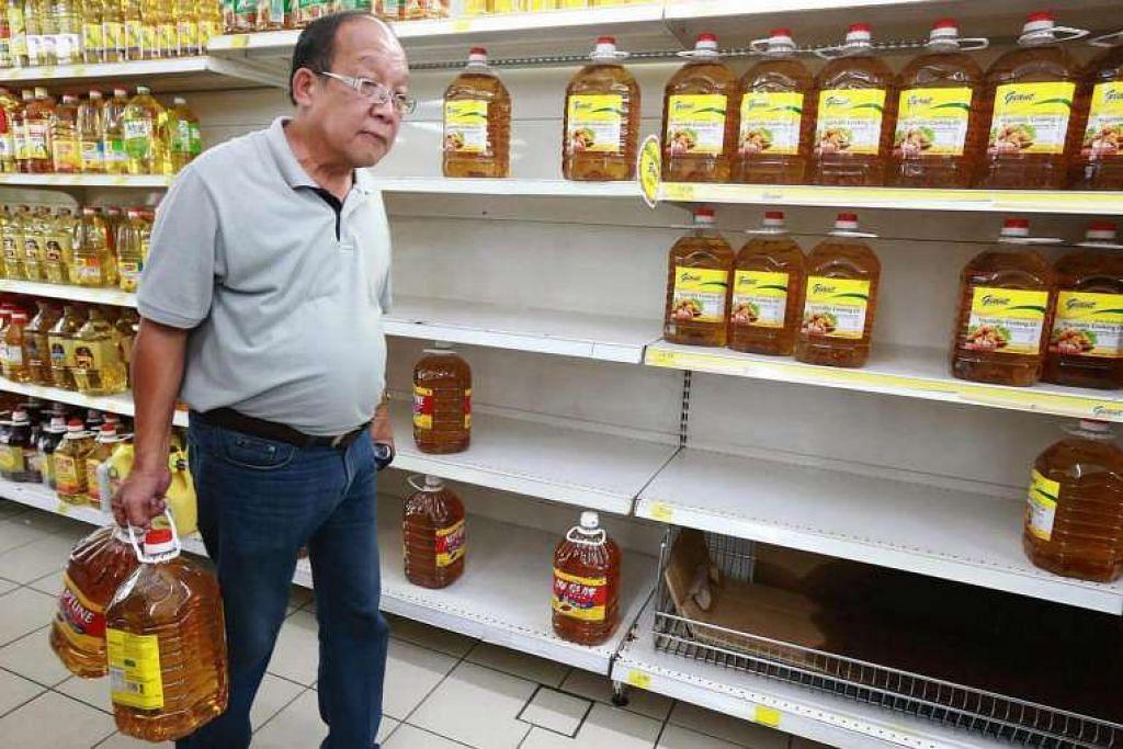 Seorang pembeli membawa dua botol minyak masak  di sebuah pasar raya di Malaysia.