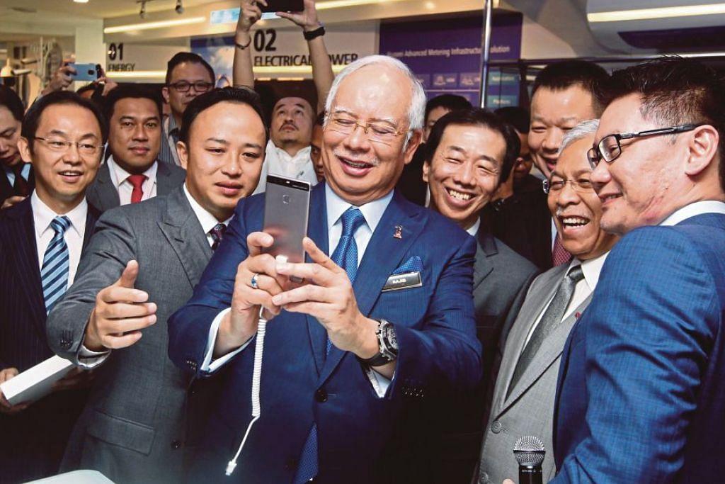 Datuk Seri Najib mencuba telefon Huawei selepas merasmikan Pusat Integrasi Penyelesaian Pelanggan dan Pengalaman Huawei (CSIC) baru di Integra Tower @ the Intermark, Jalan Tun Razak, pada 26 Oktober 2016.