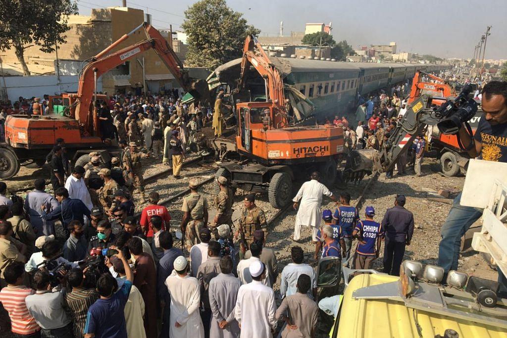Pekerja penyelamat menggunakan jentera berat dalam operasi menyelamat apabila dua kereta api bertembung di Karachi,