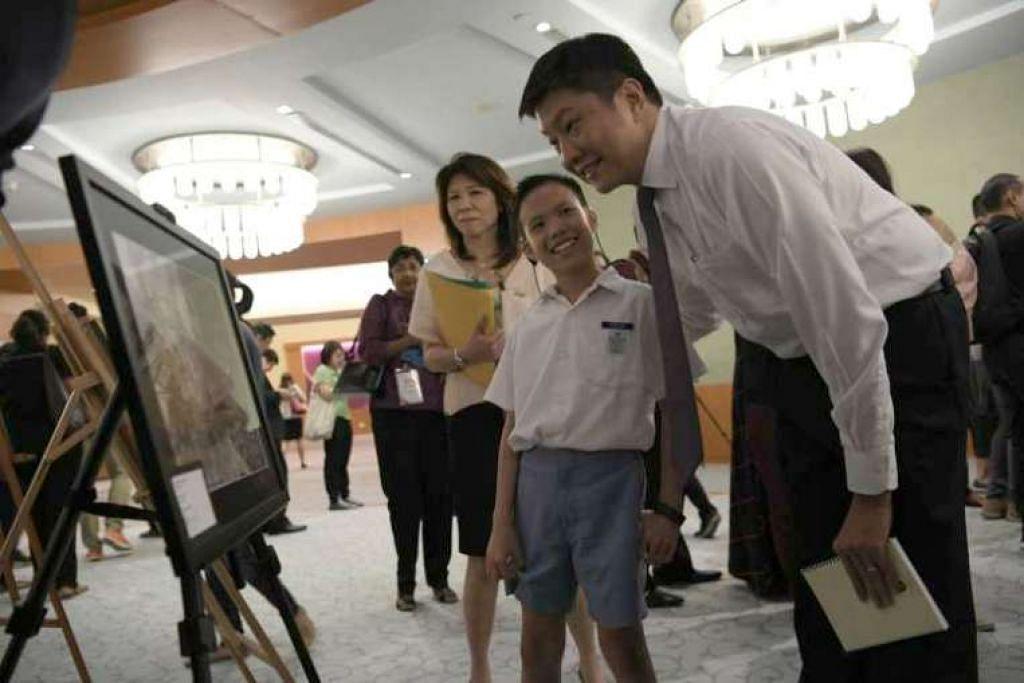 Menteri Pendidikan (Sekolah) Ng Chee Meng beramah-tamah dengan Loknaroshni, 11 tahun, yang melukis sebuah model kapal terbang.