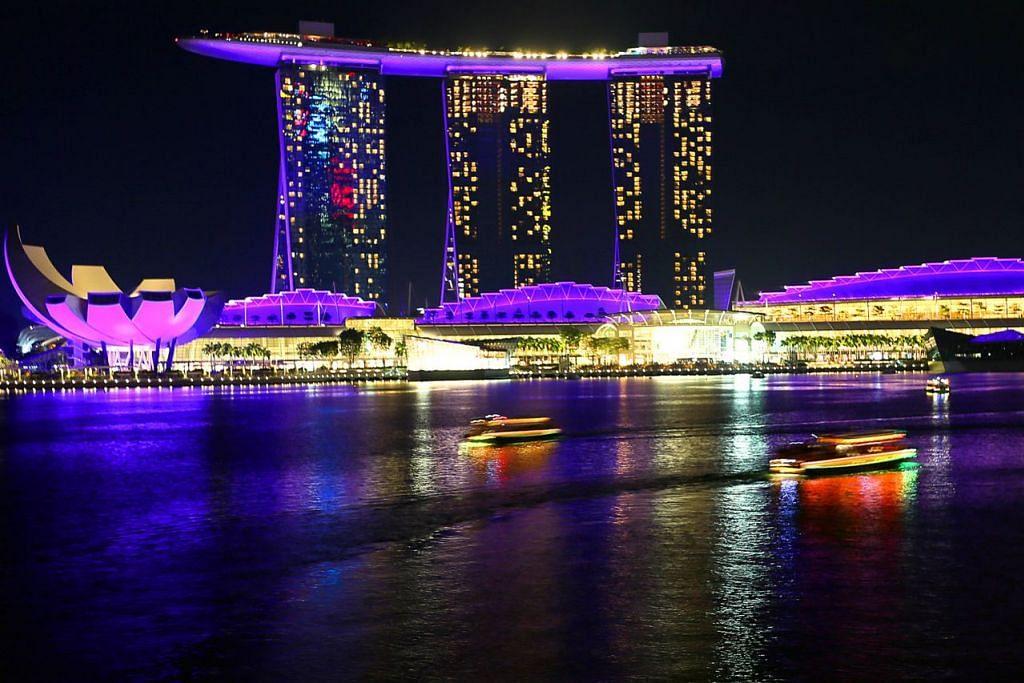 BERSELIMUT UNGU: Bangunan dan jambatan di sekitar kawasan Marina Bay diterangi lampu ungu bagi menyokong pergerakan The Purple Parade. Antara bangunan dan jambatan yang terlibat termasuk Marina Bay Sands, Hotel Fullerton dan jambatan The Helix. – Foto THE NEW PAPER