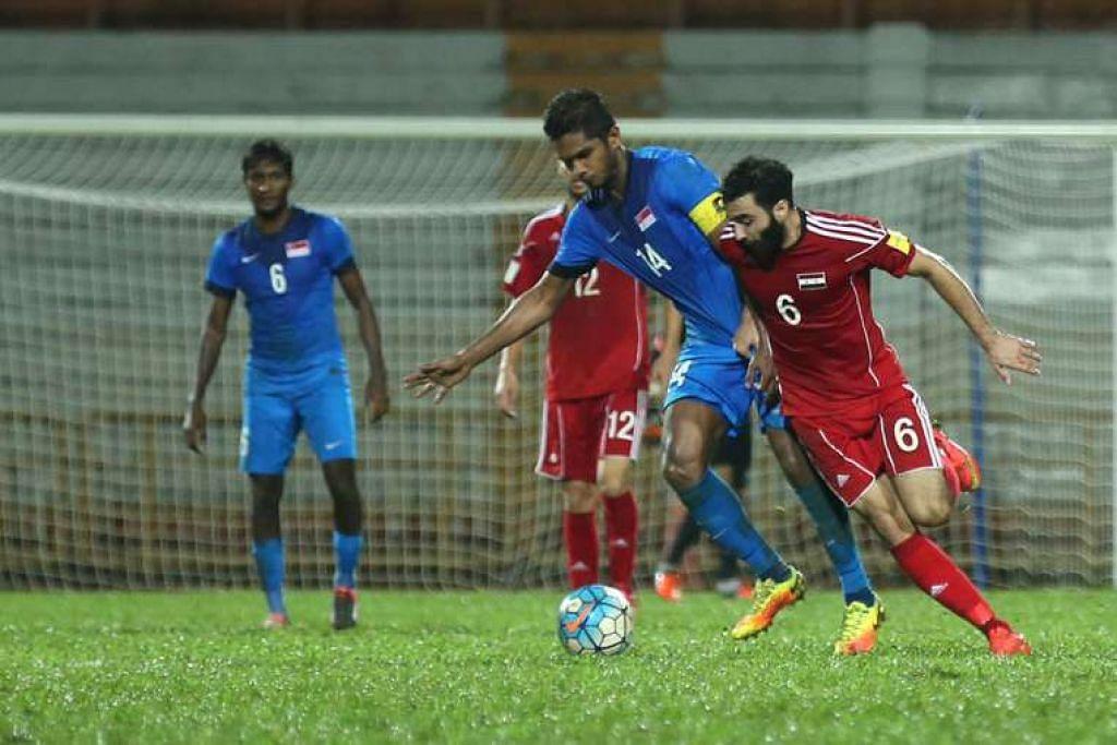Kapten Singapura, Hariss Harun (jersi biru),  merebut bola bersama Amro Jeniat, yang menjaringkan gol pertama Syria, yang menang 2-0 dalam satu perlawanan persahabatan di Paroi, Seremban.