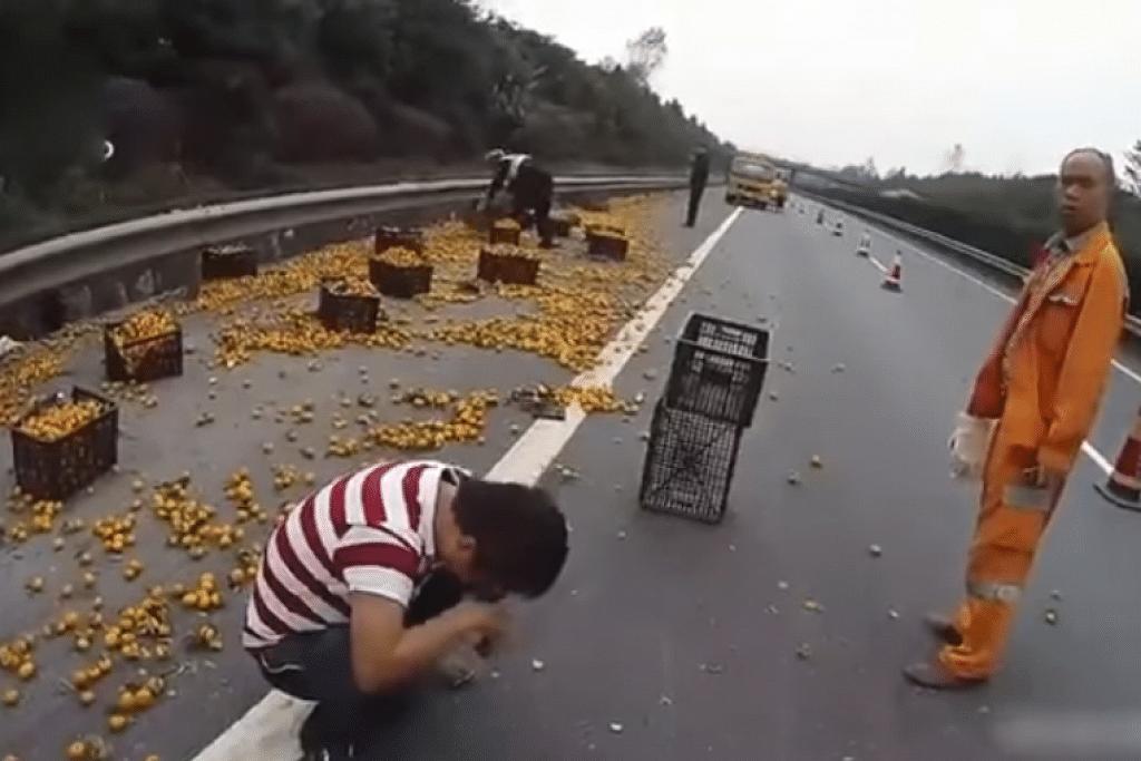 Pemandu di China ini hanya mampun menangis apabila lorinya terbalik dan penduduk kampung segara datang bukan untuk membantu tetapi mencuri buah oren yang dibawanya. SCREENGRAB DARI YOUTUBE