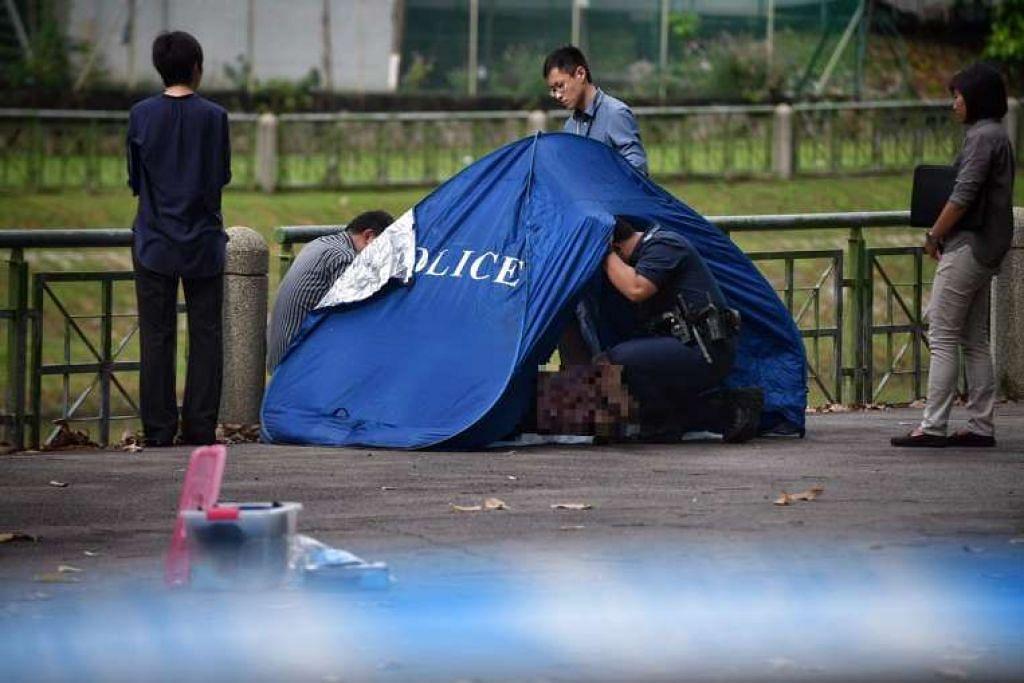 Pegawai polis memeriksa mayat yang ditemui.