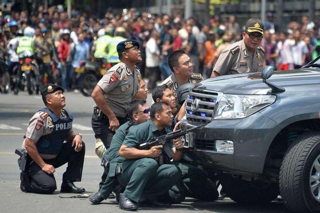Polis mengambil kedudukan di belakang sebuah kenderaan semasa mengejar suspek serangan pengganasa di Jakarta pada 14 Januari 2016, apabila lapan orang, termasuk empat pengganas, terbunuh.