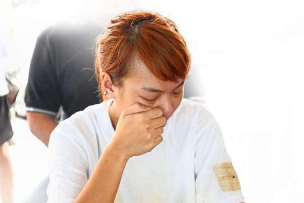 Anak perempuan mendiang Fong Meng Tuck menangis di upacara pengebumian - tanpa mayat - beliau di Maccallum Street, Penang.