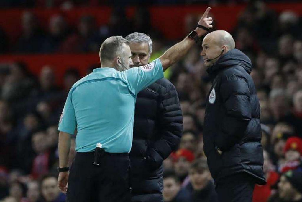 Pengurus Manchester United Jose Mourinho (menghadap kamera) dihantar ke tempat duduk penonton oleh pengadil Jonathan Moss.