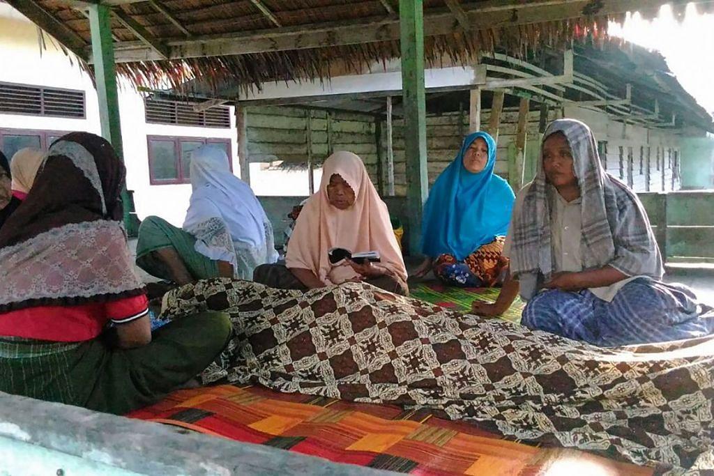 Saudara-mara berkumpul di sekitar mayat seorang mangsa yang terbunuh selepas gempa bumi  melanda bandar Pidie, wilayah Aceh, pada 7 Disember 2016.
