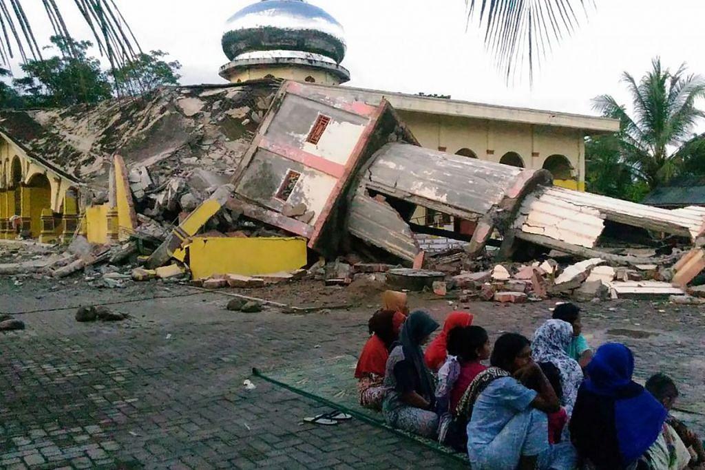 Penduduk berkumpul di luar sebuah masjid yang roboh selepas gempa bumi melanda bandar Pidie, wilayah Aceh, pada 7 Disember 2016.