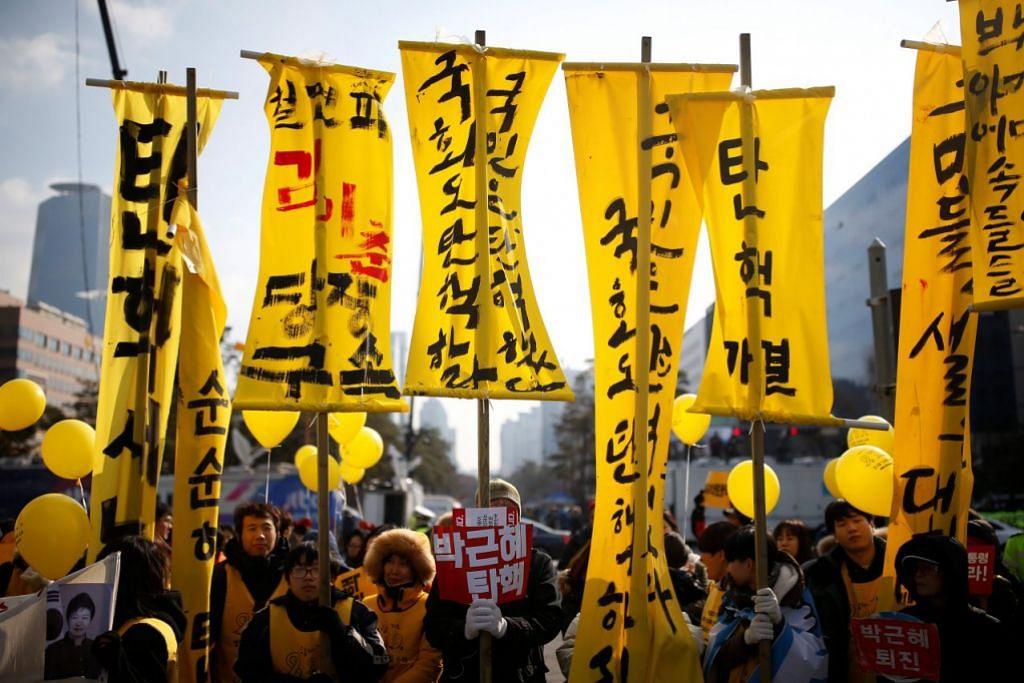 BANTAHAN RAKYAT: Penunjuk perasaan berkumpul di luar bangunan Parlimen di Seoul sambil menuntut agar Cik Park dipecat. – Foto REUTERS