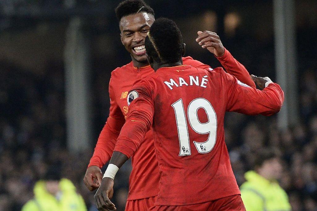 MERAIKAN KEMENANGAN:  Mane dan Sturridge berpeluk keriangan selepas beliau memanfaatkan rembatan Daniel Sturridge yang terkena palang dan menjaringkan gol kemenangan buat The Kop dalam perlawanan menentang Everton yang berkesudahan 1-0 pada awal pagi tadi. - Foto AFP