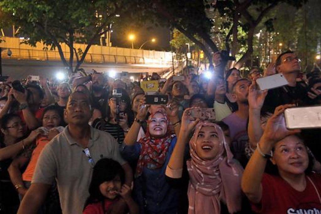 DI SINGAPURA - RAKAM KENANGAN: Orang ramai bersengkang mata agar tidak terlepas menyambut kemeriahan sambutan Tahun Baru 2016 di Marina Bay. – Foto ZAOBAO