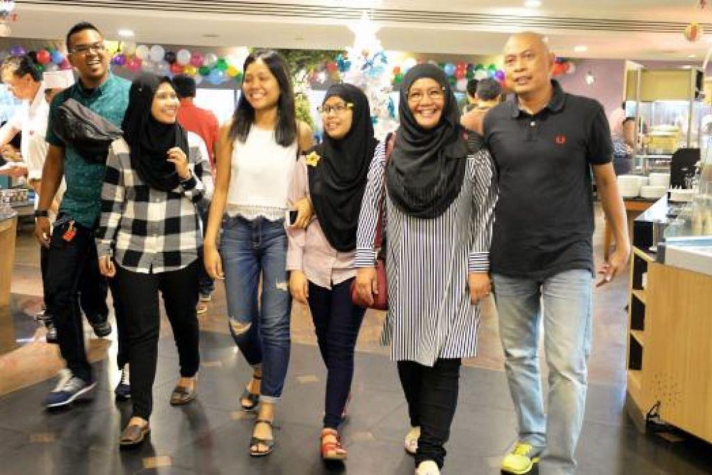 CUTI DI SINGAPURA: Cik Nur Sabreena (tiga dari kiri) dan ibunya, Cik Azlina (dua dari kanan), serta anggota keluarga mereka menginap di Hotel Furama City Centre untuk meraihkan tahun baru. - Foto: M.O. SALLEH