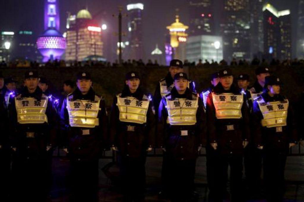 DI SERATA DUNIA... BERJAGA-JAGA: Para pegawai polis berkawal di tapak kejadian rempuhan yang membunuh 36 orang semasa sambutan tahun baru tahun lalu di Bund di Shanghai, China. Tiada sambutan di lokasi itu bagi meraikan Tahun Baru 2016. – Foto-foto REUTERS