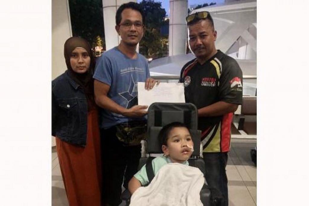 TERHARU: Encik Abdul Halim (berbaju biru) bersama isterinya, Cik Nuraini Abdul Rahman, dan anak keduanya, Syahriz Matin, berada di lobi KKH untuk menerima sumbangan derma daripada ketua Sizzlers Sg, Encik Muhd Faizal Sanwan. - Foto: SIZZLERS SG