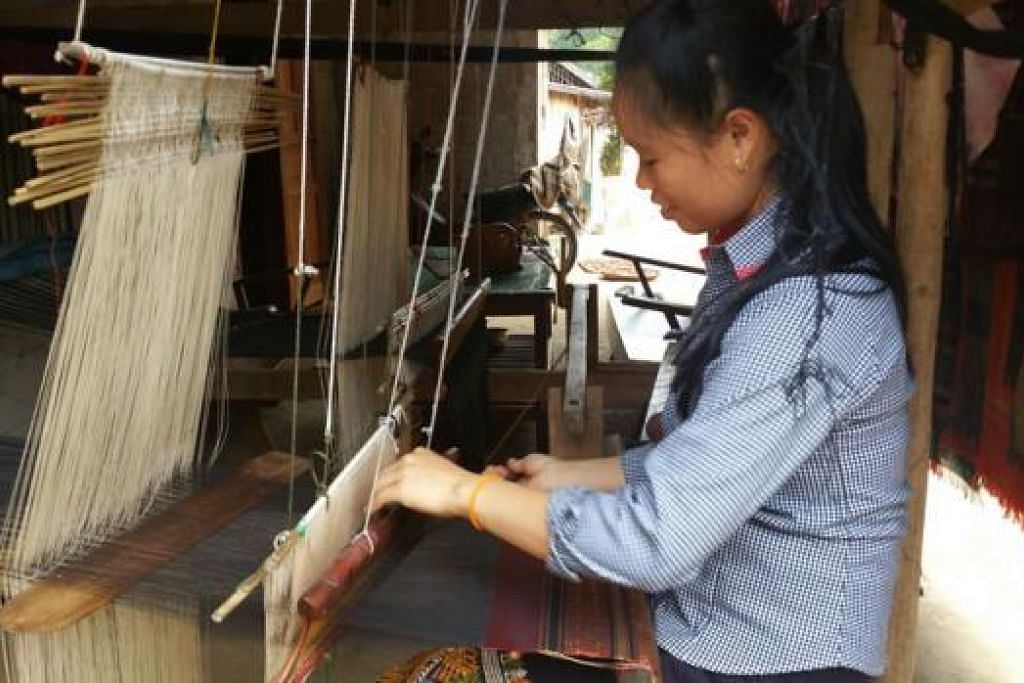 TENUN KAIN: Di kampung Ban Sop Jam, hampir setiap wanita pandai menenun kain. Kain-kain itu kemudian dipamerkan di luar rumah mereka untuk dijual.