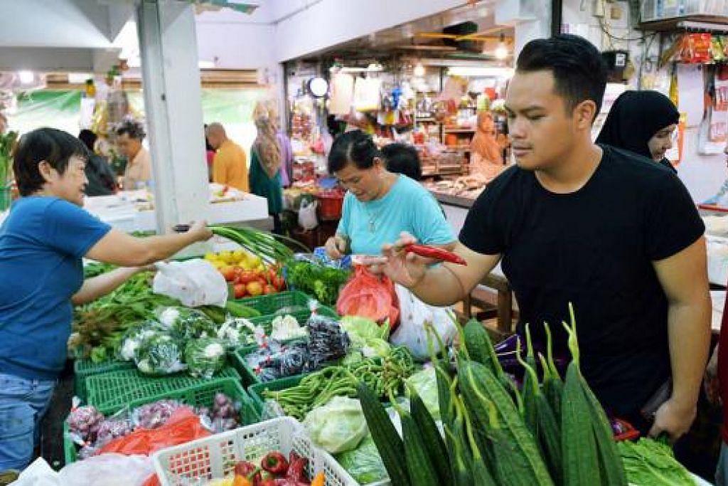 TIDAK KEKOK DI PASAR: Encik Azfar kerap ke pasar basah berbanding pasar raya kerana suka suasananya yang riuh-rendah dan mesra. - Foto KHALID BABA