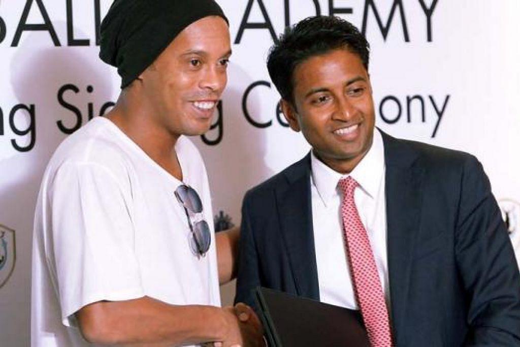SALAM KERJASAMA: Pengerusi baru Tampines, Krishna Ramachandra (kanan), bersalaman dengan bintang bola sepak Brazil, Ronaldinho, semasa memeterai satu kerjasama yang akan menyaksikan bekas Pemain Terbaik Dunia itu melancarkan akademi bola sepaknya di sini. - Foto fail